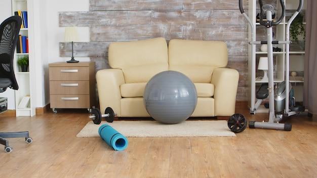 Eliptyczna piłka fitness i eliptyczna w pokoju, w której nikogo nie ma.