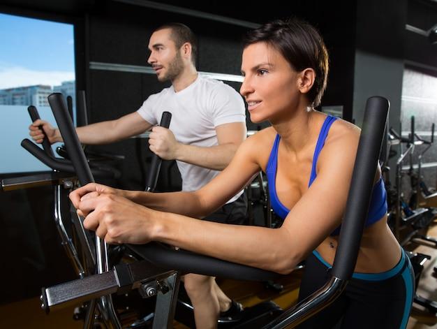 Eliptyczny trener walker mężczyzna i kobieta w czarnej siłowni