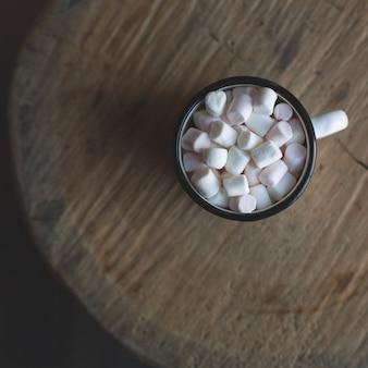 Emalia rocznika kubek z gorącym napojem świątecznym i ptasie mleczko stoi na drewnianym okrągłym cięciu. widok z góry.