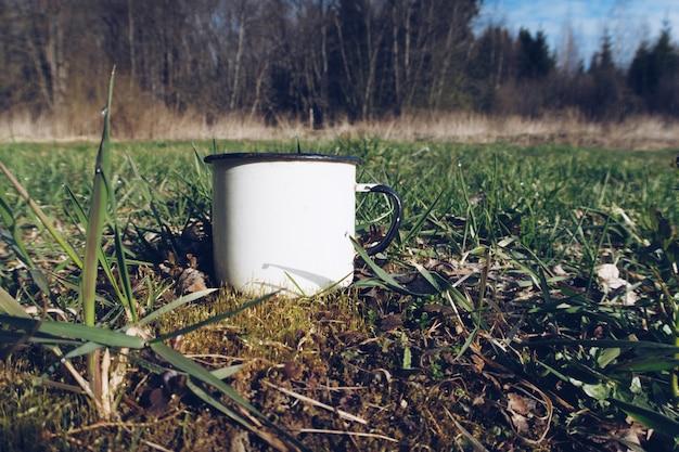 Emaliowany biały kubek na trawie w lesie