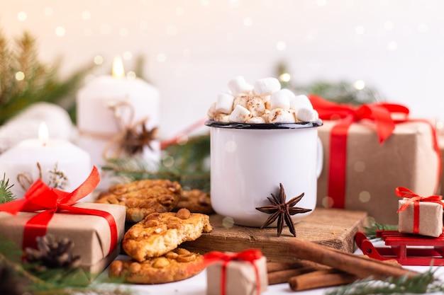 Emaliowany kubek gorącego kakao lub kawy z piankami i ciasteczkami. dookoła gałęzie drzew, prezenty i płonące świece. świąteczny nastrój. pocztówka lub tło zima.