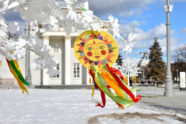 Emblemat słońca z kolorowymi wstążkami na gałęziach białego drzewasymbol karnawału na białym drzewie