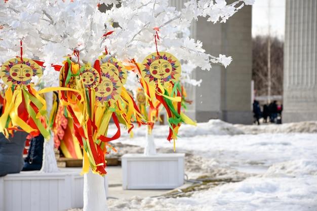 Emblemat słońca z kolorowymi wstążkami na gałęziach białego drzewasymbol karnawału