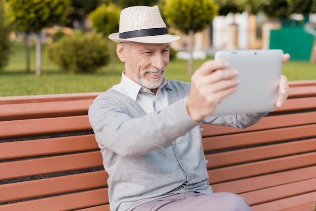 Emeryt komunikuje się z kimś za pomocą wideo.