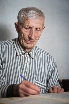 Emeryt. portret starszego mężczyzny piszącego w zeszycie