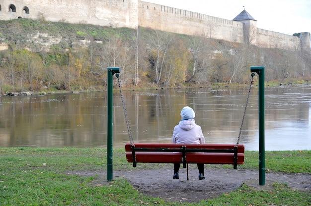 Emeryt starsza kobieta siedzi na ławce i patrzy na rzekę i starożytną fortecę