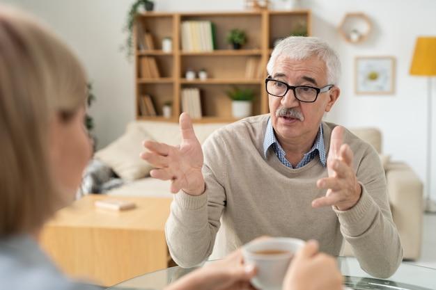 Emeryt wyjaśnia coś swojej córce podczas rozmowy przy herbacie w salonie