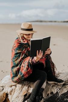 Emerytowana kobieta czytająca książkę na świeżym powietrzu