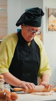Emerytowana kobieta kucharz za pomocą drewnianego wałka do gotowania pizzy. szczęśliwy starszy piekarz z bonete przygotowujący surowe składniki do pieczenia tradycyjnej pizzy posypywania, przesiewania mąki na stole w kuchni.