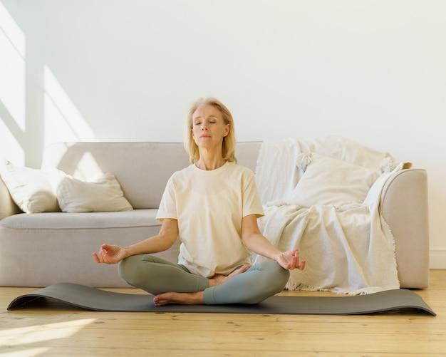Emerytowana kobieta medytuje i ćwiczy jogę siedząc w pozycji lotosu na podłodze w domu