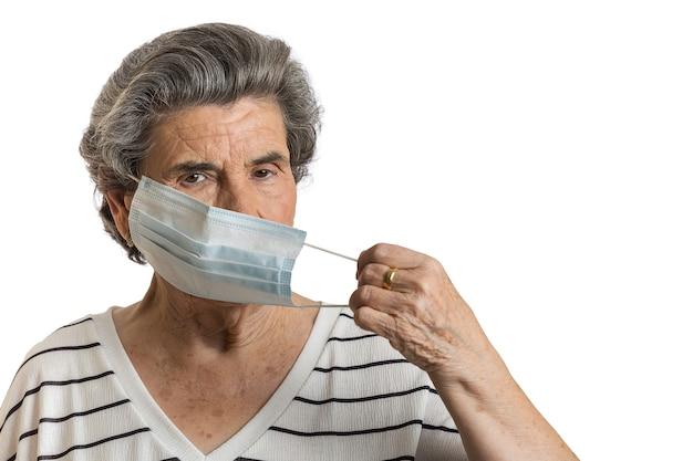 Emerytowana kobieta nosząca ochronną maskę medyczną