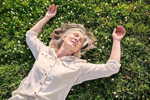 Emerytowana kobieta relaksuje się na zielonym trawniku