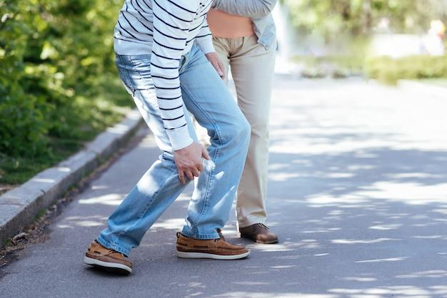 Emerytowana pomocna starsza kobieta opiekująca się chorym mężczyzną i wspierająca go stojąc na świeżym powietrzu