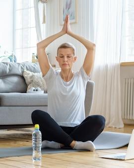Emerytowana starsza kobieta cieszy się jogą samorealizacji w domu wellness w domu