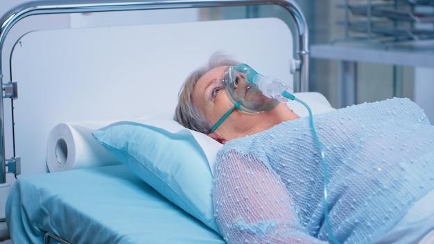 Emerytowana starsza kobieta oddychająca z maską tlenową, leżąca w szpitalnym łóżku, leczona z powodu infekcji. koronawirus covid-19 medycyna medyczna pandemia system opieki zdrowotnej