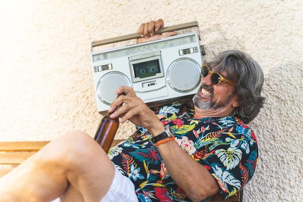 Emerytowany człowiek słucha muzyki ze starej kasety radiowej i dobrze się bawi.