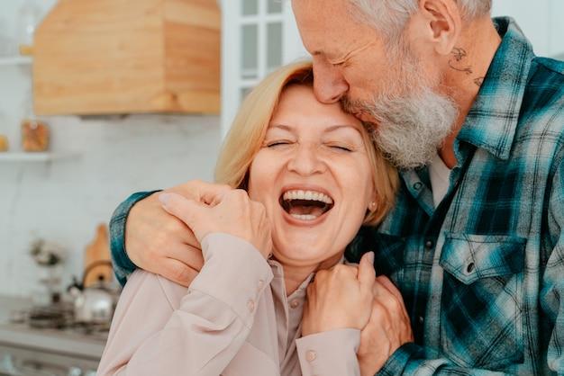 Emerytowany mąż i żona przytulają się w domu