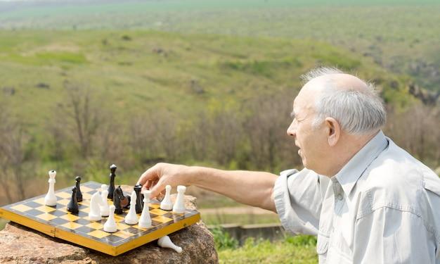 Emerytowany mężczyzna gra w szachy na wsi