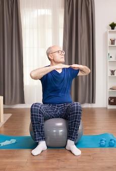 Emerytowany mężczyzna o zdrowym stylu życia, wykonujący ćwiczenia ramion