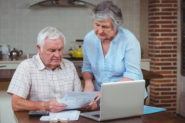 Emerytowany para obliczania rachunków z laptopem