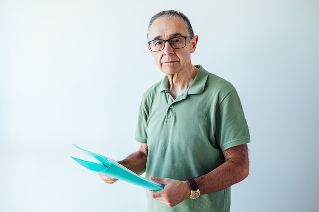 Emerytowany przedsiębiorca ubrany w zieloną koszulkę polo trzymający folder z raportem patrząc na kamery