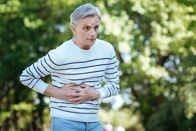 Emerytowany sfrustrowany nieszczęśliwy mężczyzna dotykający swojego brzucha i wyrażający frustrację podczas bólu brzucha na świeżym powietrzu