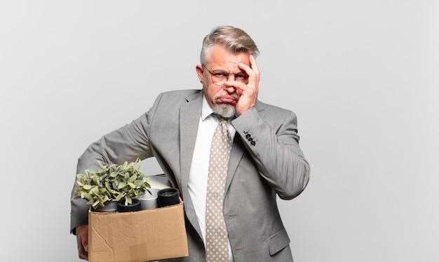 Emerytowany starszy biznesmen czuje się znudzony, sfrustrowany i senny po męczącym, nudnym i żmudnym zadaniu, trzymając twarz ręką