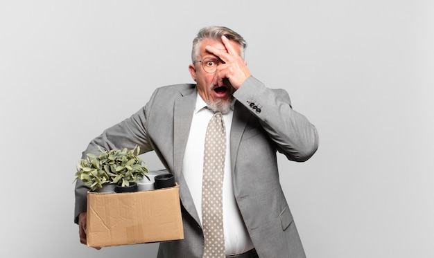 Emerytowany starszy biznesmen wyglądający na zszokowanego, przestraszonego lub przerażonego, zakrywający twarz dłonią i zerkający między palcami