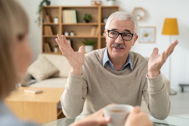Emerytowany starszy mężczyzna w codziennym stroju i okularach, który wyjaśnia coś swojej córce, pijąc herbatę w domu