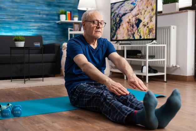 Emerytura starszy mężczyzna siedzący na macie do jogi rozciągający mięśnie nóg podczas treningu ciała
