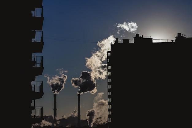 Emisja krajobrazowa do atmosfery z rur przemysłowych. komin o wschodzie słońca w bloku mieszkalnym budynku mieszkalnego. elektrociepłownia parowa lub dymna w mieście. globalne ocieplenie i zanieczyszczenie powietrza