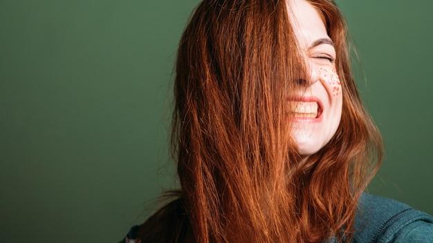 Emocja kobiety. grymas twarzy. młoda rudowłosa kobieta z obnażonymi zębami