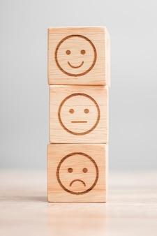 Emocja symbol twarzy na drewnianych klockach. ocena usług, ranking, ocena klientów, satysfakcja, ocena i koncepcja informacji zwrotnych