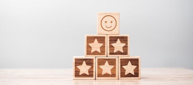 Emocja twarz i symbol gwiazdy bloki na tle tabeli. ocena usług, ranking, ocena klientów, satysfakcja, ocena i koncepcja informacji zwrotnych