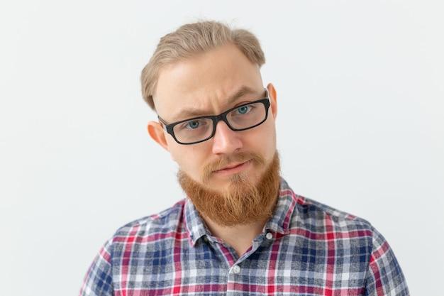 Emocje i koncepcja ludzi - portret poważnego mężczyzny z czerwoną brodą na białej powierzchni
