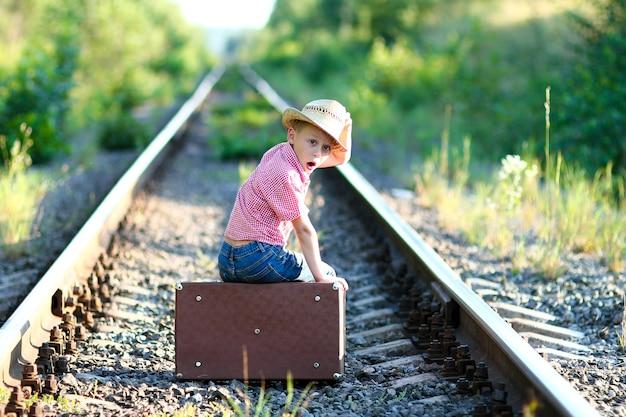 Emocje kowbojskie chłopca z walizką i koncepcją zachodniej podróży kolejowej