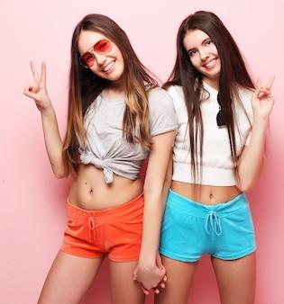 Emocje, ludzie, nastolatki i koncepcja przyjaźni - dwie piękne młode dziewczyny nastolatki, dając znak zwycięstwa