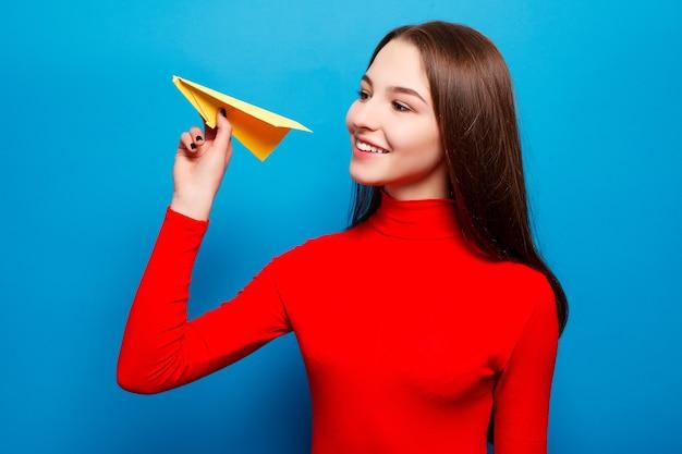 Emocje, ludzie, uroda, moda i styl życia, podróże, turystyka i koncepcja ludzie - portret pięknej kobiety trzymającej żółty papierowy samolot. na niebieskim tle.