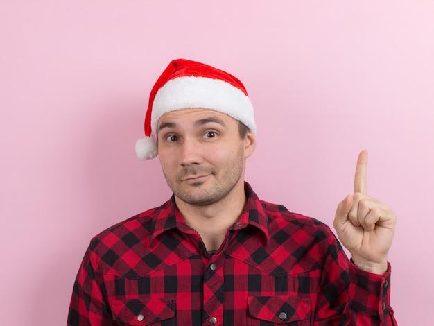 Emocje na twarzy, zadumane, odbicie, plan, pomysł. mężczyzna w kraciastym króliku i świątecznym czerwonym kapeluszu