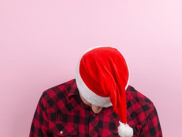 Emocje na twarzy, zmęczony, wakacyjny kac, świadomość. mężczyzna w kraciastym króliku i świątecznym czerwonym kapeluszu