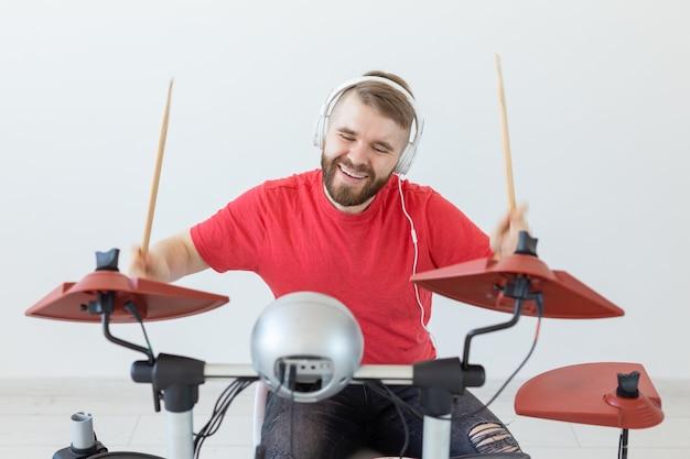 Emocje, perkusja elektroniczna i koncepcja ludzie - młody perkusista mężczyzna gra na bębnie.