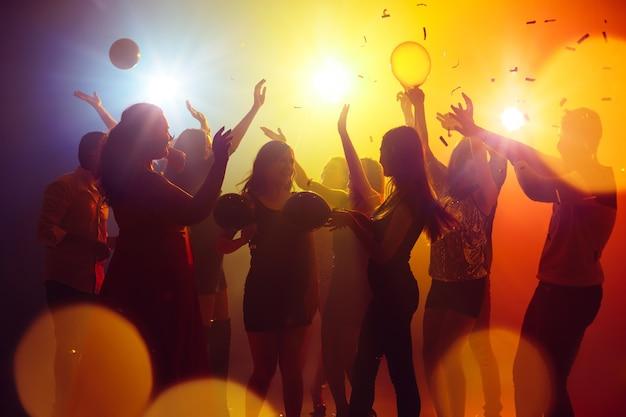 Emocje. tłum ludzi w sylwetce podnosi ręce na parkiecie na neonowym tle. życie nocne, klub, muzyka, taniec, ruch, młodzież. żółto-niebieskie kolory i poruszające dziewczyny i chłopcy.