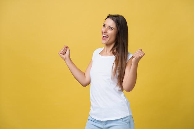 Emocje, wyrażenia, koncepcja sukcesu i ludzi - szczęśliwa młoda kobieta lub nastolatka świętuje zwycięstwo na białym tle na żółtym tle.