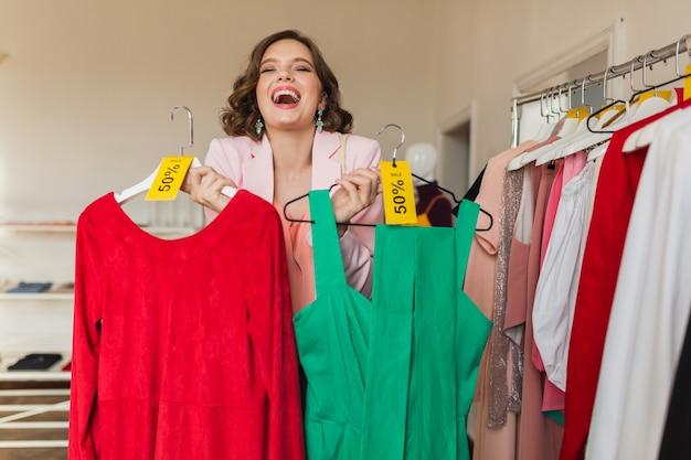 Emocjonalna atrakcyjna kobieta trzyma kolorowe sukienki na wieszaku w sklepie odzieżowym