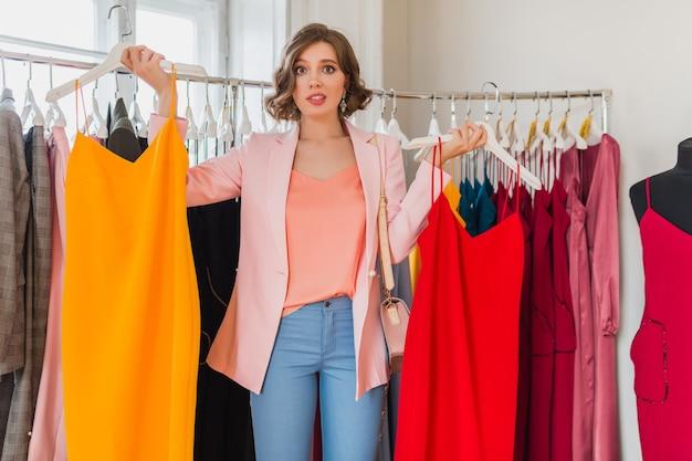 Emocjonalna atrakcyjna szczęśliwa kobieta trzymając kolorowe sukienki w sklepie odzieżowym