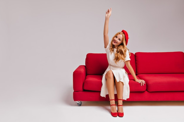 Emocjonalna biała dziewczyna w ślicznym berecie siedzi na kanapie. wesoły blondynka pozowanie na kanapie z ręką do góry.