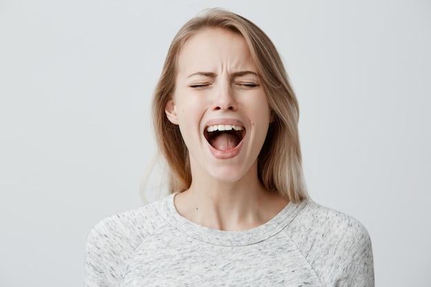 Emocjonalna blond kobieta szeroko otwierająca usta krzyczy głośno, niezadowolona z czegoś wyrażającego nieporozumienie i irytację