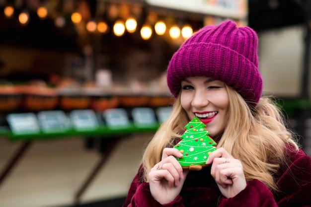 Emocjonalna blondynka trzyma słodkie świąteczne pierniczki, pozuje na jasnym tle dekoracji