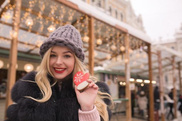 Emocjonalna blondynka trzymająca aromatyczny świąteczny piernik na tle lekkiej dekoracji na jarmarku bożonarodzeniowym w kijowie