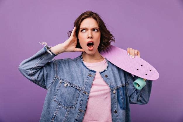 Emocjonalna brązowowłosa dziewczyna w dżinsowym stroju, trzymając longboard. kryty zdjęcie jocund modelki z zmartwionym wyrazem twarzy.